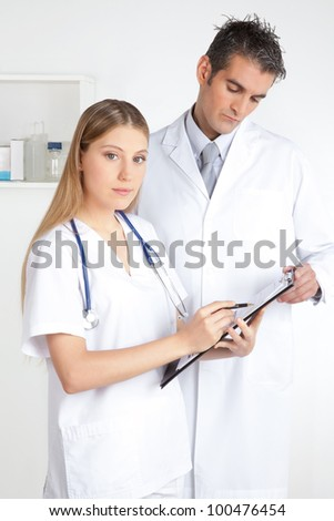Female doctor showing clipboard to the male doctor. - stock photo