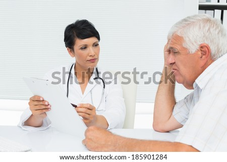 Female doctor showing reports to senior patient at medical office - stock photo