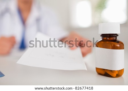 Female doctor showing sheet of paper next to pills