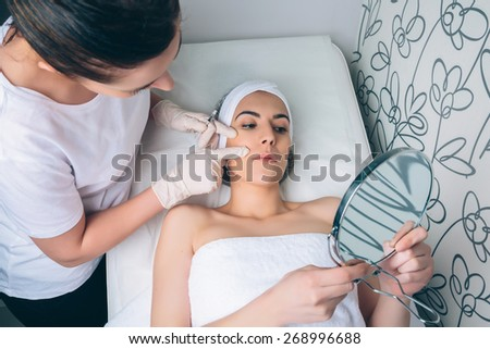 Female doctor showing to young pretty woman the face zones to apply clinic treatment. Medicine, healthcare and beauty concept. - stock photo