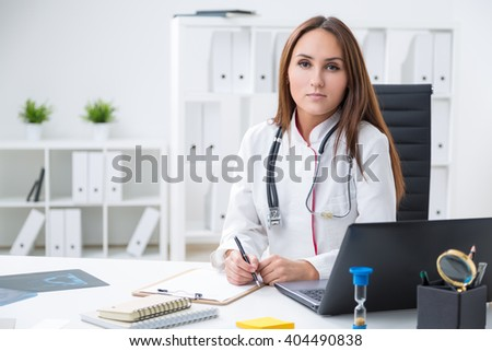 Female doctor sitting at table. Office at background. Concept of work. - stock photo