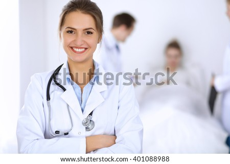 Female doctor smiling on the background with patient in the bed and two doctors - stock photo