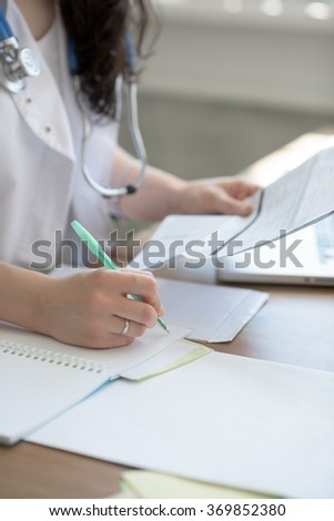 Female doctor taking notes during looking at patient medical tests at her office - stock photo