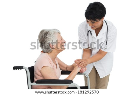 Female doctor talking to a senior patient in wheelchair over white background - stock photo