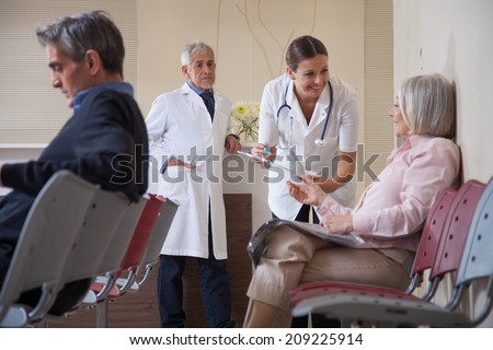 Female doctor talking to patient in waiting room. - stock photo
