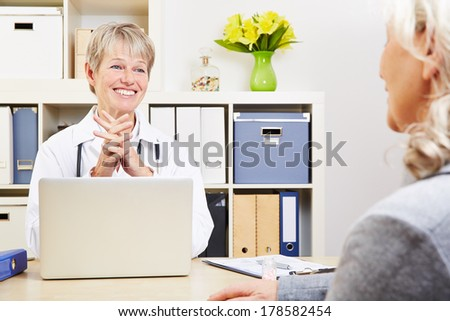 Female doctor talking with senior patient in her office - stock photo