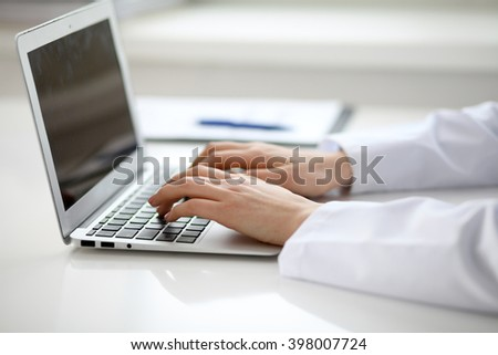 Female doctor typing on laptop, close up