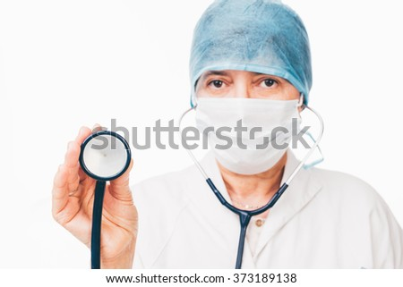 Female doctor wearing a cap is holding a stethoscope in her hand - isolated on white