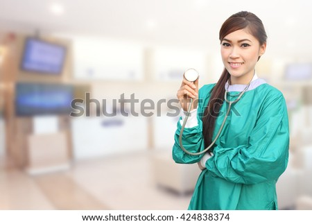 female doctor wearing a green scrubs and stethoscope in hospital background - stock photo