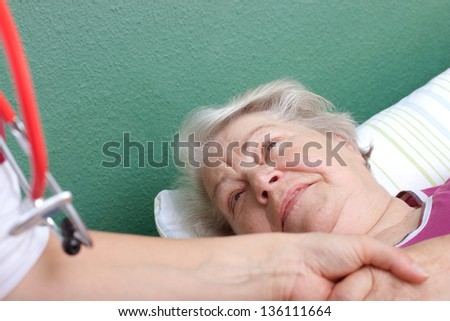 female Doctor welcomes senior lying in bed - stock photo