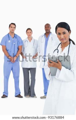 Female doctor with clipboard and colleagues behind her against a white background