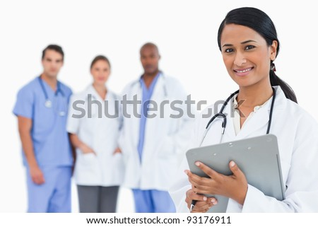 Female doctor with clipboard and staff members behind her against a white background