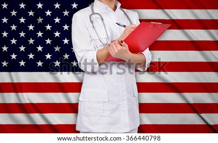 female doctor with clipboard on usa flag background - stock photo