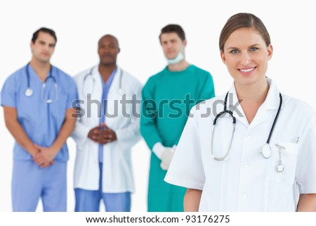 Female doctor with colleagues behind her against a white background