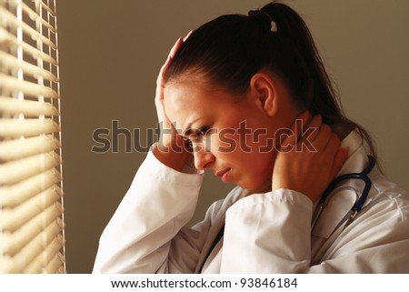 Female doctor with head pain standing near window - stock photo