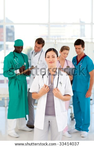 Female doctor with her team in the background in hospital - stock photo