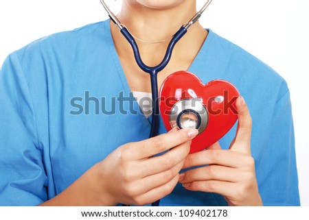 Female doctor with stethoscope holding heart - stock photo