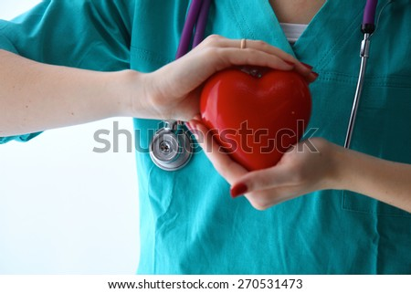 Female doctor with stethoscope holding heart over white background.