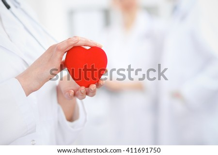Female doctor with stethoscope holding heart.  Two doctors standing in the background - stock photo