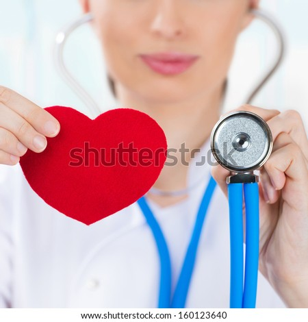 Female doctor with stethoscope holding red human heart at hospital - stock photo