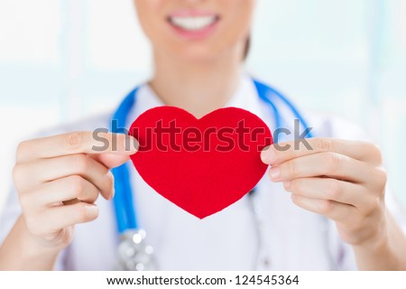 Female doctor with stethoscope holding red human heart at hospital, life insurance and follow up program concept - stock photo