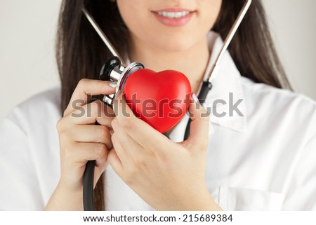 Female Doctor With Stethoscope Listening To The Heartbeat - stock photo