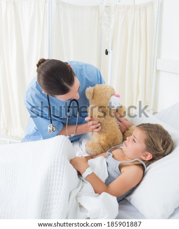 Female doctor with teddy bear entertaining sick girl in hospital bed