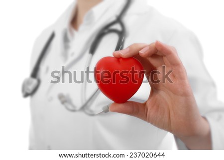 Female doctor with the stethoscope holding heart - stock photo