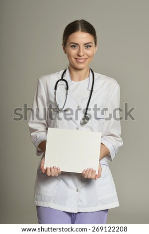 Female doctor with white list, standing on grey background