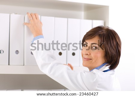 Female doctor working at office, smiling.