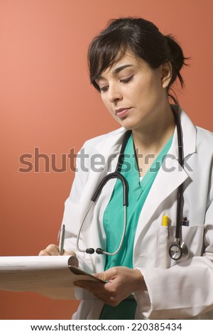 Female doctor writing notes - stock photo