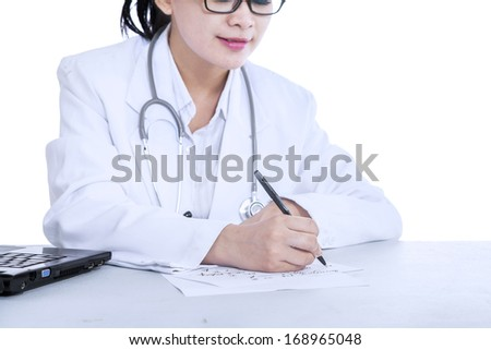 Female doctor writing notes with a notebook at the desk, isolated on white