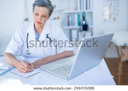 Female doctor writing on paper in medical office