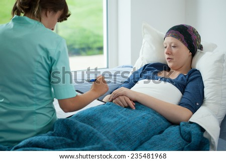 Female doctor writing the test results in the patient's card - stock photo