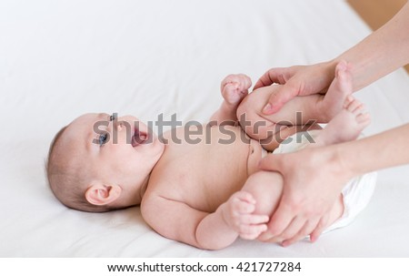 Female doing massage and gymnastic baby