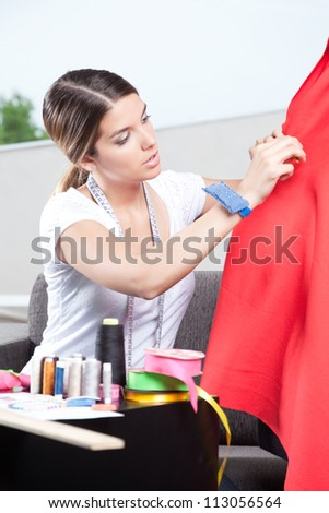 Female dressmaker adjusting clothes on tailoring mannequin. - stock photo