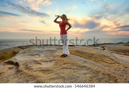 Female drinking bottled water outdoors by the ocean with pretty sky behind her