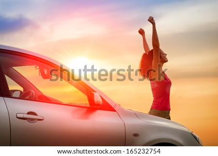 Female driver beside car raising arms and feeling the freedom of driving towards the sunset.  Woman and vehicle on beautiful sunshine background. - stock photo