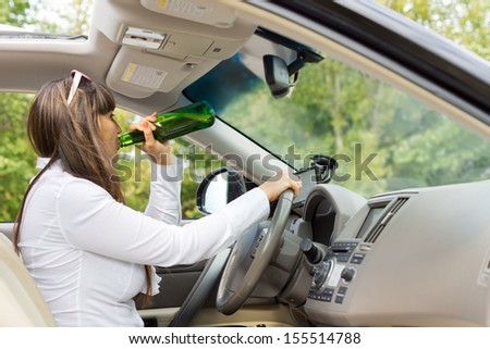 Female driver drinking alcoholic spirits upending the bottle and gulping down the booze as she tries to steer her car at the same time - stock photo