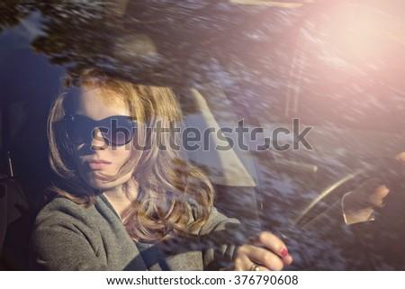 Female driver driving a car - stock photo