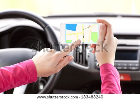 Female driver hand holding a smart phone with a GPS  navigator on the screen. - stock photo