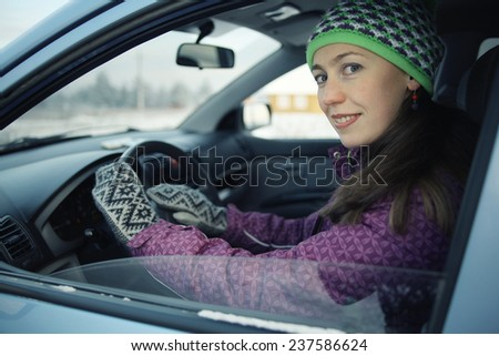 female driver in the car in winter - stock photo