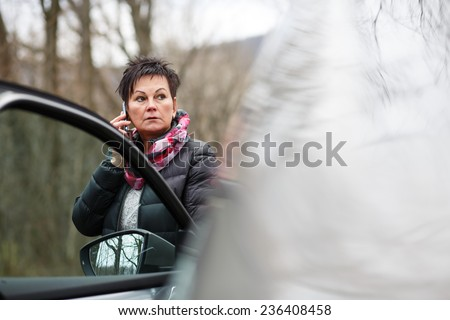 Female Driver Making Phone Calls After Traffic Accident. Woman dialing her phone after car breakdown problem. Mechanic crash - stock photo