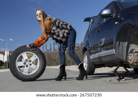 Female driver repairs car. Young female, dressed in jeans pants, red sweater and fur vest, rolls big wheel from the broken car.