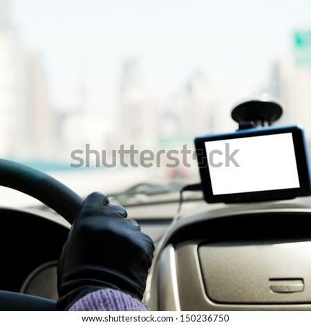 Female driver's hands on steering wheel inside of a car, using a satelite navigation/GPS.  - stock photo