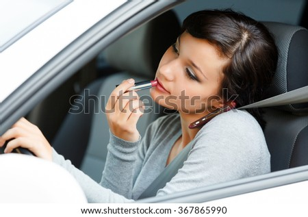 Female driver talking by mobile telephone and doing make-up. - stock photo