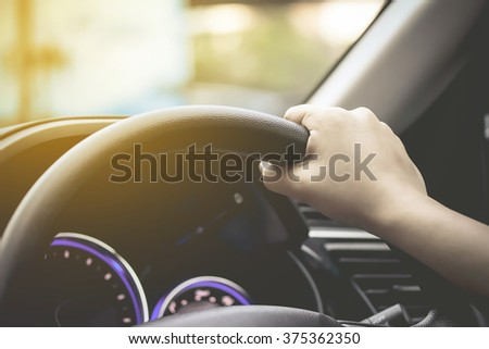 female driving car (right driver) - stock photo