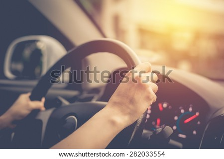 Female driving car. Vintage filter - stock photo