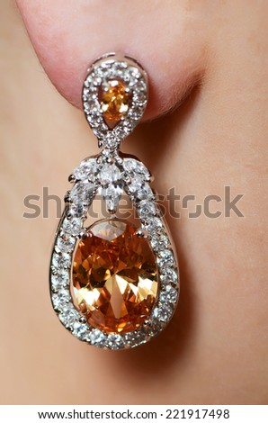 Female ear in jewelry earrings close up - stock photo