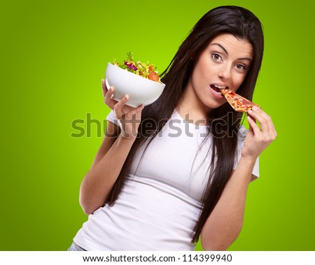 Female Eating A Piece Of Pizza And  Holding A Salad Bowl On A Green Background